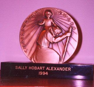 The front of the Christopher Medal shows St. Christopher, ready to cross the water, carrying the little boy who grows heavier and heavier because he turns out to be Jesus. At the base, my name and the year 1994 are engraved.