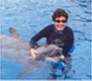 This is the second of four thumbnail photos of me swimming with and stroking a dolphin